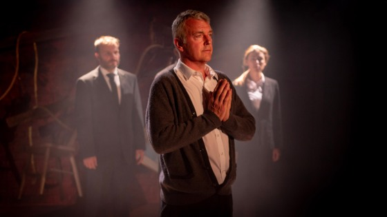 A character prays whilst others are in the background.