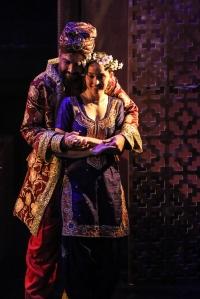 King Shahryar embraces Sharazad from behind