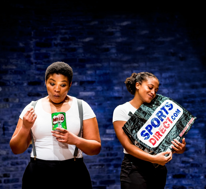 Two women, one eating out of a Milo tin and one holding a Sports Direct bag